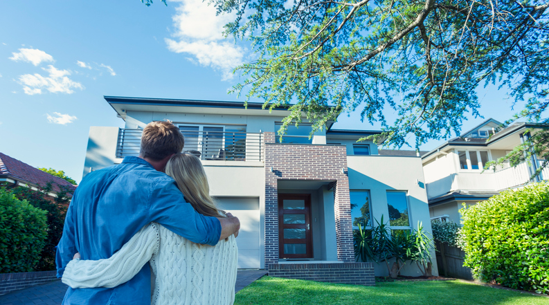 Couple standing in front of their new home
