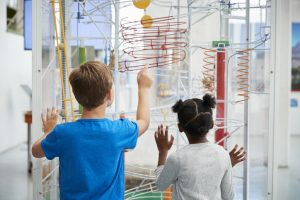 Two kids looking at a science exhibit, back view